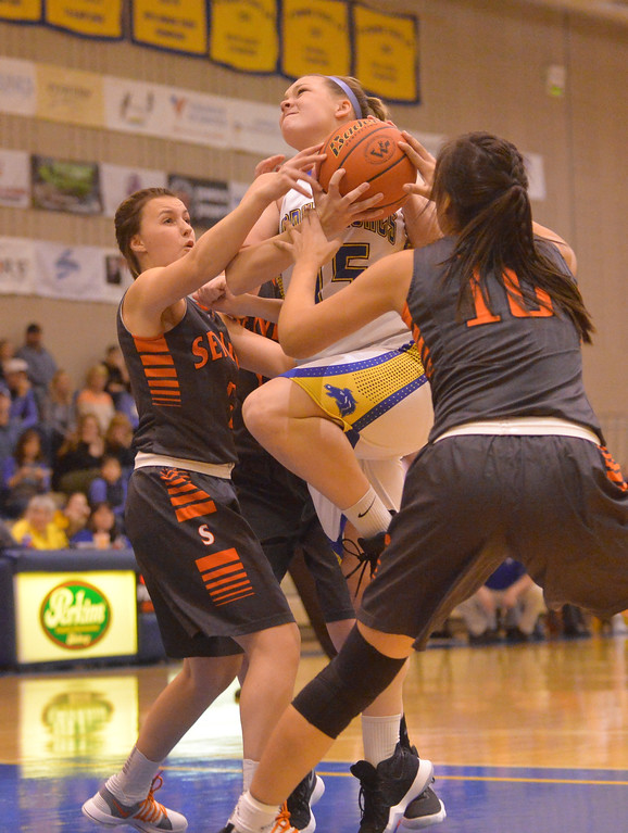 Justin Sheely | The Sheridan Press<br /> Sheridan's Kailee Ingalls is fouled by Senior High School's Mariah Linse, left, and Kola Bad Bear during their home opener at Sheridan High School Friday, Dec. 15, 2017. The Lady Broncs lost to Billings Senior 64-59.