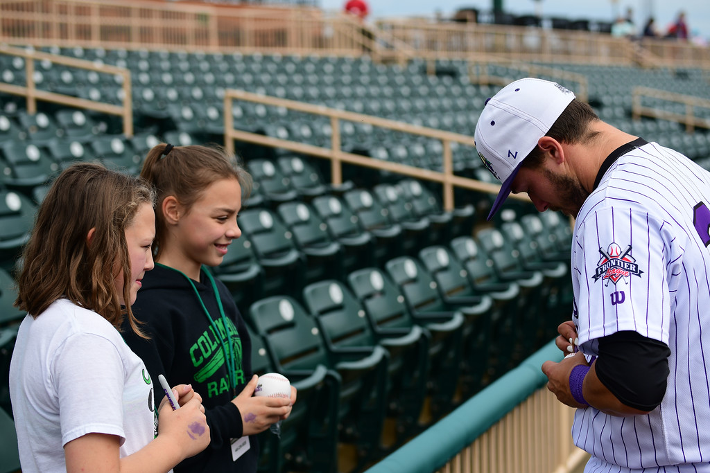 . Eric Bonzar�The Morning Journal<br> Catcher Brian Mayer signs autographs for 10-year-olds Bailey Gonia, left, and Olivia Meier, during the Crushers\' home opener, May 15, 2018. The two attended the game with their fellow classmates from Copopa Elementary School, in Columbia Station.