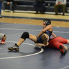 RYAN HUTTON/ Staff photo. <br /> Lawrence's Yeriel Cruz (in blue) moves to pin Winchester's Tom Donley (in red) during the 113 pound weight class match at Lawrence High School on Saturday.