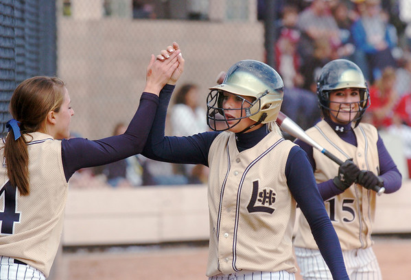 Legacy's Kaitlyn Mattila, center, is congratulated by Melissa Marcovecchio, left, after scoring the winning run in the state 5A softball game against Ralston Valley on Saturday at the Aurora Sports Park. <br /> October 24, 2009<br /> Staff photo/David R. Jennings