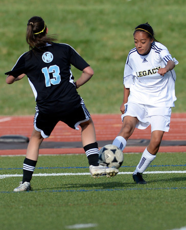 Legacy's Ariana Jimenez (right) takes a shot on goal past Mountain Range's Jose Matlick (left) during their soccer game in Westminster, Colorado May 1, 2012. CAMERA/MARK LEFFINGWELL