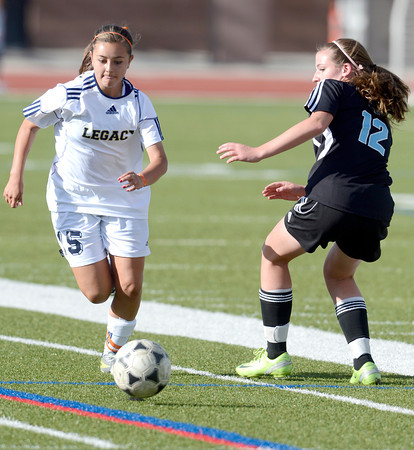 Legacy's Brooke Williams (left) takes the ball past Mountain Range's Sara Goodman (right) during their soccer game in Westminster, Colorado May 1, 2012. CAMERA/MARK LEFFINGWELL