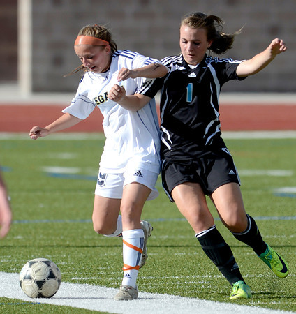 Legacy's Mady Huber (left) races Mountain Range's Jesse McKenna (right) to the ball during their soccer game in Westminster, Colorado May 1, 2012. CAMERA/MARK LEFFINGWELL
