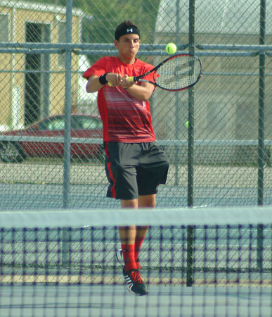 Rushville's Chase Hamilton hits a backhand return during action at No. 1 doubles.