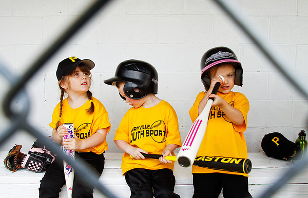 From left, Pirates Haley Rogers, 4, Hayden Jaggers-Geralds, 4, and Kyrsten Adkins, 4, pay attention to everything but tee ball while waiting to bat during their game on opening day of the Henryville Youth Sports baseball and softball season in Henryville on Saturday. The opening ceremonies were held after a weather delay, but more rain moved through the area in the mid-afternoon and most of the scheduled games had to be called off. Staff photo by Christopher Fryer