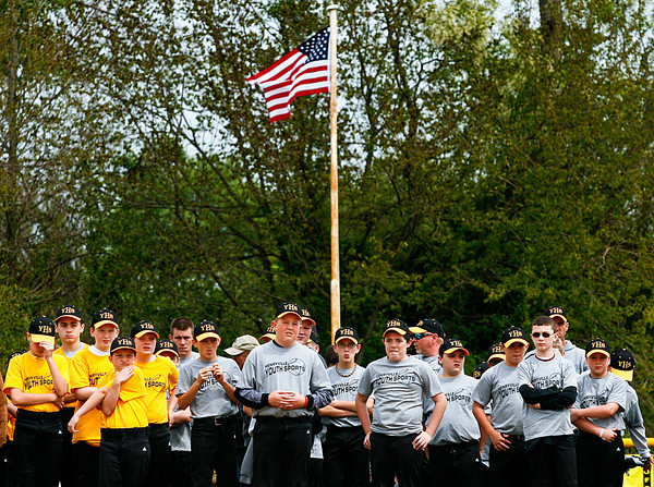 An American flag flys above Henryville Youth Sports baseball players as they stand in the outfield during the opening ceremonies of the baseball and softball season in Henryville on Saturday afternoon. The opening ceremonies were held after a weather delay, but more rain moved through the area in the mid-afternoon and most of the scheduled games had to be called off. Staff photo by Christopher Fryer
