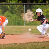 New Albany's Trevor Laughead comes to a stop just past second base while Silver Creek's Jake Jackson misses the ball during the fifth inning of their game in the District V Little League All-Stars tournament in Charlestown on Saturday afternoon. Silver Creek won the game 9-8. Staff photo by Christopher Fryer