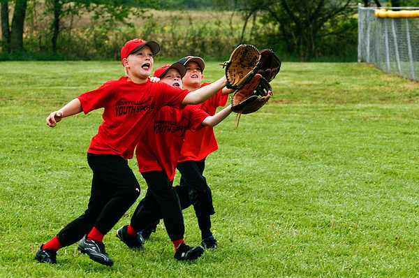 From left, Taylor Guthrie, 8, Tayton Guthrie, 6, and Mikel Sterling, 7, scramble for a fly ball while horsing around before the opening ceremonies of the Henryville Youth Sports baseball and softball season in Henryville on Saturday morning. The opening ceremonies were held after a weather delay, but more rain moved through the area in the mid-afternoon and most of the scheduled games had to be called off. Staff photo by Christopher Fryer