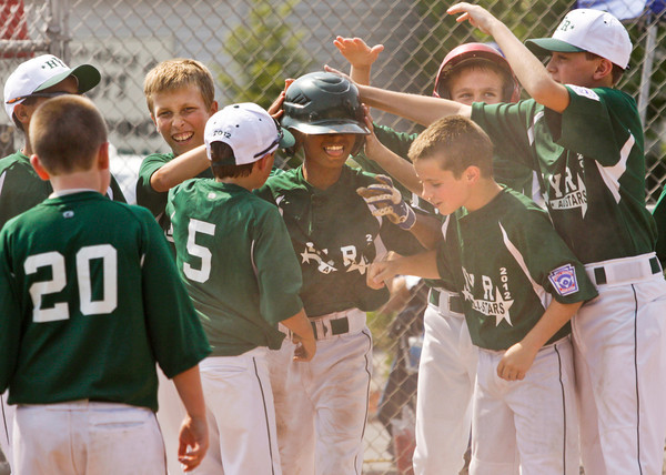 Highlander Youth Recreation's Noah Franklin is congratulated by his teammates after hitting a home run in the fifth inning of their game against New Albany during the 11-year-old District V Little League All-Star tournament in Charlestown on Saturday afternoon. HYR won the game 12-5. Staff photo by Christopher Fryer