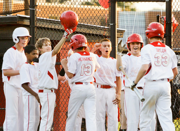 Jeff/GRC's Drew Taylor is congratulated by his teammates after hitting a two-run-homer during their game against New Albany in the 11-12-year-old District 5 championship game at Mt.Tabor Park in New Albany on Tuesday. Jeff/GRC won the game, 12-3. Staff photo by Christopher Fryer