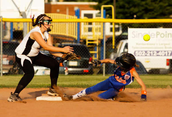 New Albany's Bre Scoenfield misses a catch as Silver Creek's Jordan Balz slides safely into second base during the third inning of the District 5, 11-12-year-old softball championship game at Grant Line Elementary School on Tuesday. New Albany won the game, 5-2. Staff photo by Christopher Fryer