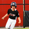 New Albany's Tucker Biven celebrates after scoring their first run of the game in the fifth inning during their 9-10-year-old District 5 championship game against Jeff/GRC in New Albany on Saturday. New Albany won the game, 3-0. Staff photo by Christopher Fryer