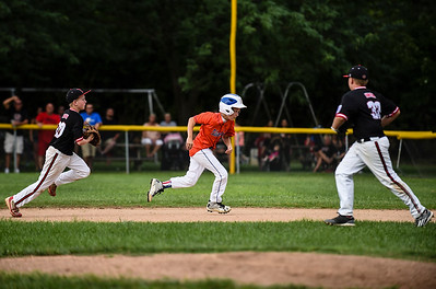 Silver Creek's Jack Beyl is caught in a pickle by New Albany infielders Cody Jackson, left, and Blaine Hamilton, right, during New Albany's 8-5 win for the District 5 Little League Minor Championship on Saturday in Sellersburg. Staff photo by Tyler Stewart