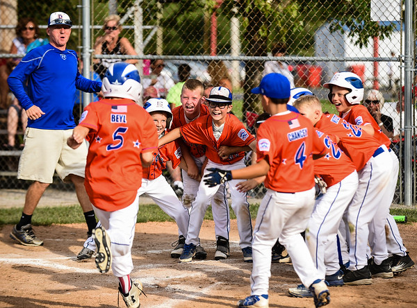 The Silver Creek dugout greets Jack Beyl at home plate following his solo home run in the third inning during New Albany's 8-5 win for the District 5 Little League Minor Championship on Saturday in Sellersburg. Staff photo by Tyler Stewart