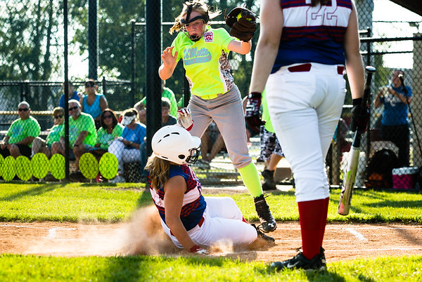 Charlestown's Karly Byrnes slides into home plate during their Junior Softball State Tournament win against DeMotte at Clarksville Little League fields on Friday.