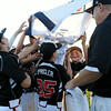 New Albany teammates hold up their championship banner after the New Albany and HYR 9-10 District 5 All-Star Championship at the Clarksville Little League Park Wednesday evening. New Albany won 5-1.<br /> Staff photo by Tyler Stewart