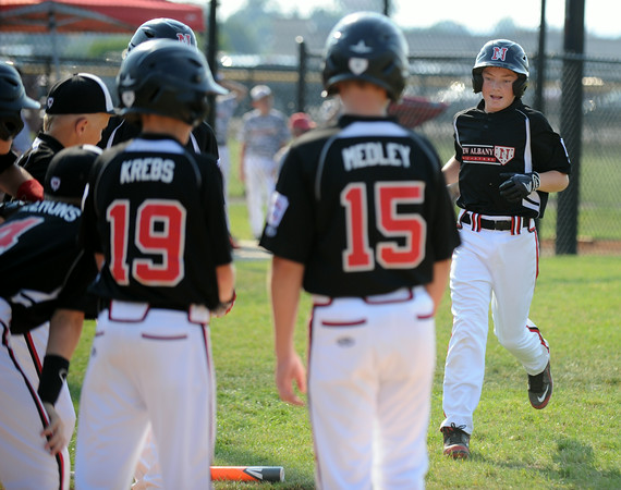 New Albany team members wait to congratulate center fielder David Newbanks after hitting a home run in the first inning during the New Albany and Silver Creek 11-12 baseball pool play game in the District 5 All-Star tournament at the Clarksville Little League Park Friday. New Albany won 15-3. <br /> Staff photo by Tyler Stewart