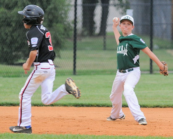 Highlander Youth Recreation All-Star Trent Allen throws to first base during Monday's District 5, 10/11 year old, pool game against New Albany. Photo by Joe Ullrich