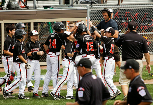 Cody Medley is congratulated by his teammates after hitting a two-run RBI single to seal New Albany's 14-4 win over Burlington, Wis. in the Great Lakes Region tournament semifinals in Indianapolis on Thursday. Staff photo by Christopher Fryer