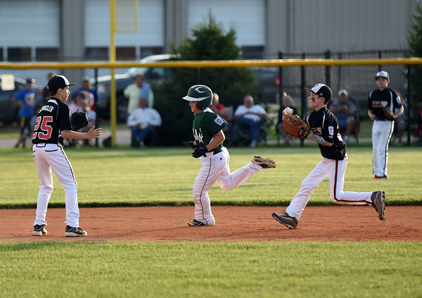 New Albany's Hunter Sprigler, left, and Max Beatty catch HYR's Garron Jenkins in a pickle play during the New Albany and HYR 9-10 District 5 All-Star Championship at the Clarksville Little League Park Wednesday evening. New Albany won 5-1.<br /> Staff photo by Tyler Stewart