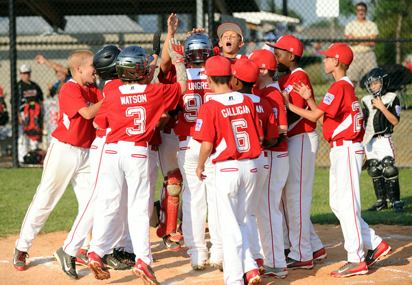 Jeff/GRC teammates celebrate after Logan Ungren's home run during the Jeff/GRC and New Albany 11-year-old baseball pool play game in the District 5 All-Star tournament at the Clarksville Little League Park Friday. <br /> Staff photo by Tyler Stewart