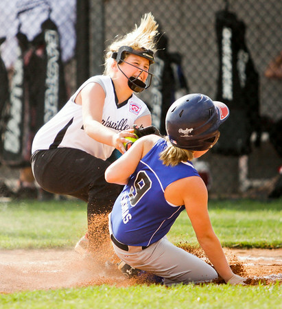 Shalynn Murphy, left, attempts to tag Madison Thomas out at home plate during Clarksville's game against Charlestown at the Clarksville Little League Park on Monday. Thomas was safe on the play. Staff photo by Christopher Fryer