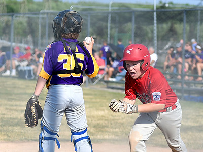 KRISTIN BAUER | CHRONICLE Elyria's Levi Ellis (9) cheers after sliding into home safely as Avon catcher Joshua Putka (36) holds the ball on Tuesday evening, July 5.