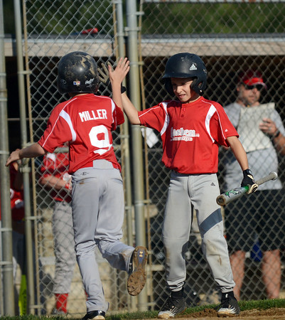 HALEY WARD | THE GOSHEN NEWS <br /> Goshen's Carter Miller high fives Myles McLaughlin after Miller scored in the Goshen vs. Bristol game on Friday at the Goshen Little League Park.