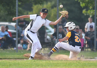 KRISTIN BAUER | CHRONICLE Avon third baseman Connor Malicki (9) narrowly misses catching a throw to tag Tallmadge's Nick Cuva (24) out at third on Wednesday night, July 12.