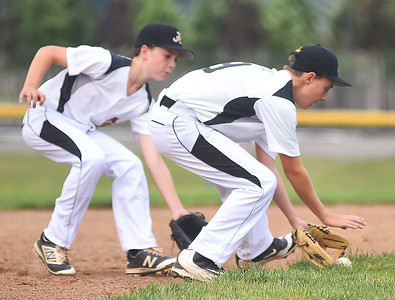 KRISTIN BAUER | CHRONICLE Avon third baseman Connor Malicki (9) scoops up a ground ball with backup from shortstop Davis Ocepek (23) hit during a game against Tallmadge on Wednesday night, July 12.
