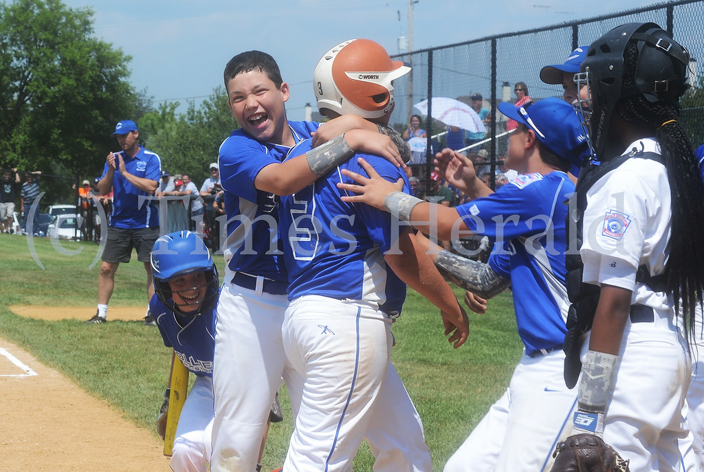 . Collier players embrace teammate Sam Tortorella after his home run.  Saturday, July 26, 2014.  Photo by Adrianna Hoff/Times Herald Staff.