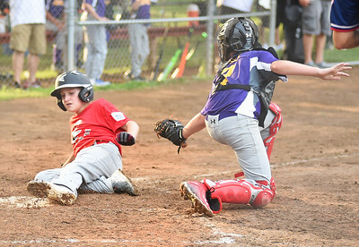 KRISTIN BAUER | CHRONICLE Elyria's Shane Putka (5) slides into home plate safely as Avon's catcher Ryan Lysle (7) attempts to lay the tag on Tuesday evening, July 11.
