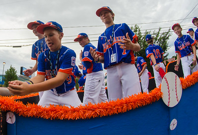 Davis Moran of the Great Lakes team catches candy while standing between teammates John Guthrie and Tate Hanks during Wednesday's Grand Slam parade.