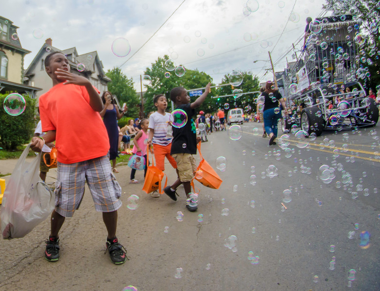 Kids play with bubbles from the Pennsylvania Food Bank float during the Grand Slam parade on Wednesday.