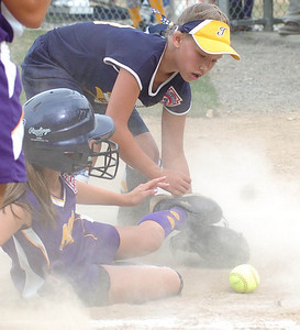 Avon's #8 Kayla Graham slides into home safely knocking the Tallmadge pitcher's #18 Jessica Herman's glove away from the ball.