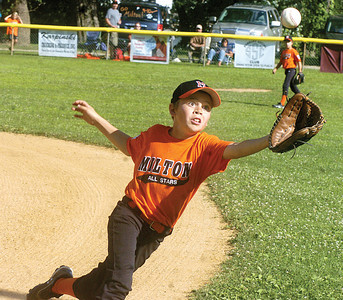 Milton's Tanner Davis reaches for a fly ball during Tuesday's game against Snyder County at the Acorn Little League Field in Northumberland.