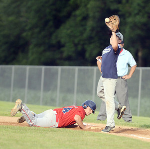 Selinsgrove's Noah Hendricks dives back to first base as Berwick's Casey Tanribler catches the ball during the Junior Division Little League game in New Berlin on Thursday evening.
