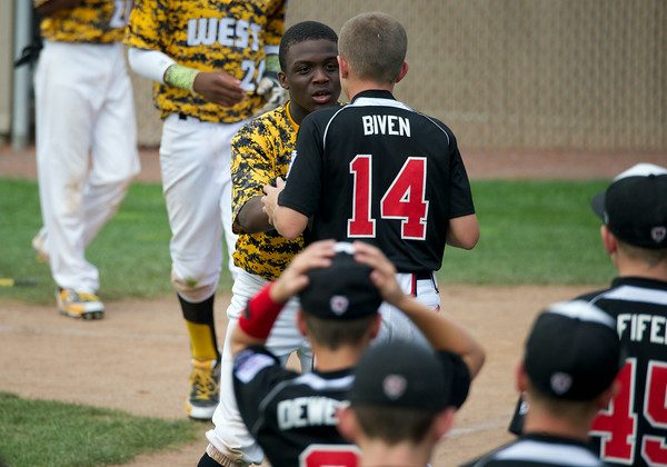 New Albany's Cooper Biven is consoled by Jackie Robinson West's Marquis Jackson after New Albany's 12-7 loss in the Great Lakes Region Championship in Indianapolis Saturday. Staff photo by Tyler Stewart