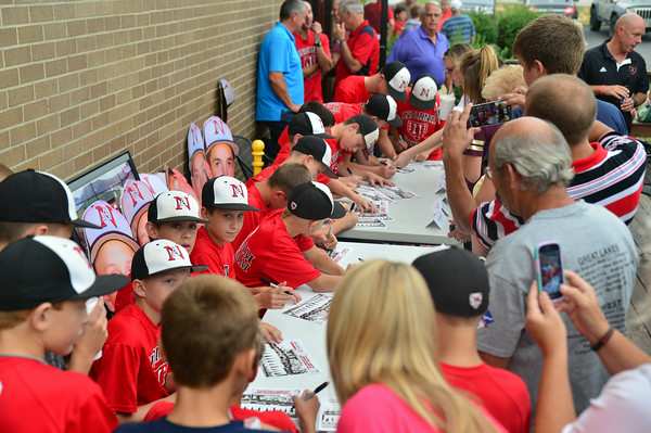 New Albany Little League fans and supporters gather around the 11-12 All Star team for pictures and autographs during the Celebration of Champions event at Bearno's Pizza in New Albany Friday evening. Staff photo by Tyler Stewart