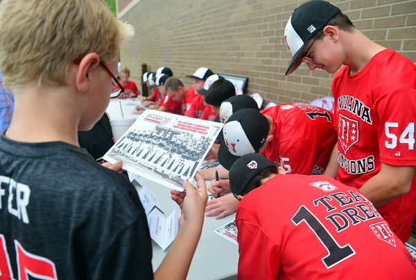 A New Albany baseball fan looks over his autographs from the 11-12 All Star players during the Celebration of Champions event and welcoming home party for the Indiana State Champions Friday evening at Bearno's Pizza in New Albany.  Staff photo by Tyler Stewart