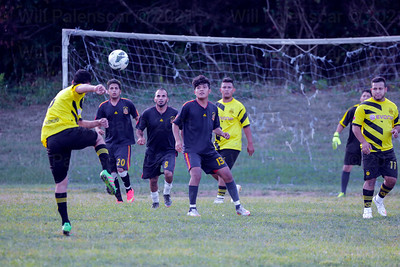A soccer player heads the ball as all others from both teams watch carefully