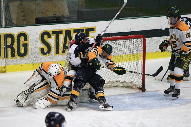 FSU Goalie Charles Jakobsson ties the puck up as FSU's James Gordon hits Joseph Berardi in the crease of the net