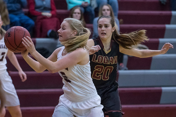 Jaci Jensen (5) dishes the ball out to a teammate while Logan High School's Kira Peterson (20) chases her down on Thursday night at Morgan High School on January 12, 2017.