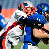 Longmont's AJ Shannon (21) is tackled by Heritage's Austin Colaizzi (56) during the class 4A state championships at Invesco Field at Mile High Stadium in Denver, Saturday, Dec. 5, 2009. Heritage High School won the title, 42-28.