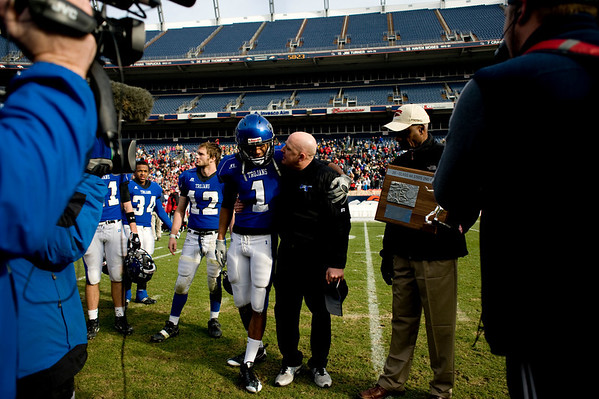 """Longmont's Devin Strauss (1) and head coach Doug Johnson recieve the second place trophy after losing to Heritage High School during the class 4A state championships at Invesco Field at Mile High Stadium in Denver, Saturday, Dec. 5, 2009. Heritage High School won the title, 42-28. <br /> <br /> For more photos, please visit  <a href=""""http://www.dailycamera.com"""">http://www.dailycamera.com</a><br />  <br /> KASIA BROUSSALIAN / THE CAMERA"""
