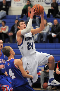 Longmont's Reilly Mau goes to the basket past Centaurus' Sam Esler during Friday's game at Longmont.  For more photos please see www.dailycamera.com January 26, 2012 staff photo/ David R. Jennings
