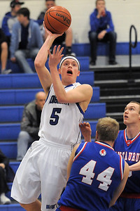Longmont's Josh Cogdill goes to the basket over Centaurus' Shane Ellingotn during Friday's game at Longmont.  For more photos please see www.dailycamera.com January 26, 2012 staff photo/ David R. Jennings
