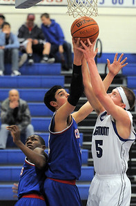 Longmont's Josh Cogdill goes to the basket against Centaurus' Austin Tunquist and Matu Giltner during Friday's game at Longmont.  For more photos please see www.dailycamera.com January 26, 2012 staff photo/ David R. Jennings