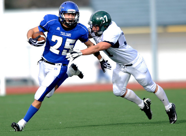 Longmont's Darian Finley-Garcia (25) pushes off Pine Creek's Clay Hildebrant (37) during the Class 4A State Quarterfinals at Longmont High School in Longmont, Saturday, Nov. 21, 2009.<br /> <br /> KASIA BROUSSALIAN /THE CAMERA