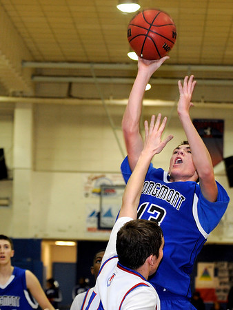 Longmont High School senior Cade Kloster takes a shot over Centaurus defenders during a basketball game against Centaurus High School on Friday, Jan. 28, in Lafayette. Longmont defeated Centaurus in double over  time.<br /> Photo by Jeremy Papasso